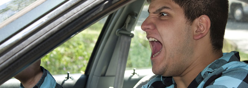 Young man screaming with road rage in his car.
