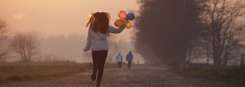 Girl walking down a park path with balloons, in the morning sun.